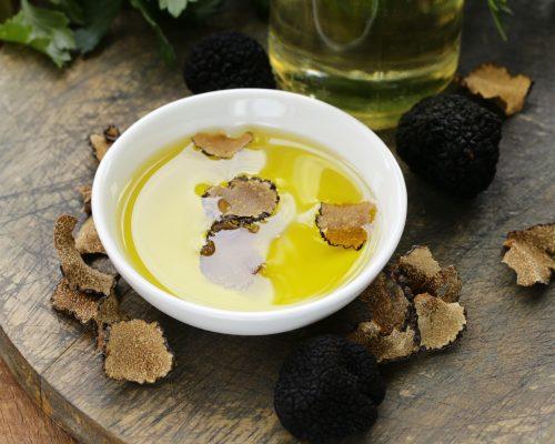 Huile d'olive aromatisée à la truffe noire sur une table en boisHuile d'olive aromatisée à la truffe noire sur une table en bois - Visit Provence