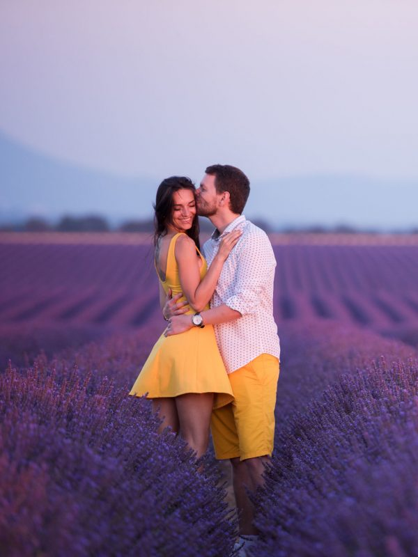 couple in purple lavender flower  field kissing and have romantic time in sunset